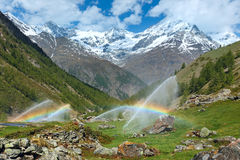 Rainbows in irrigation water spouts in Summer Alps mountain royalty free stock photos