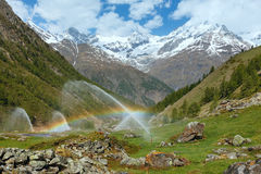 Rainbows in irrigation water spouts in Summer Alps mountain Royalty Free Stock Photography