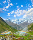 Rainbows in irrigation water spouts in Summer Alps mountain Royalty Free Stock Photo