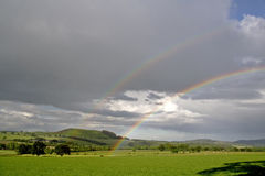 Rainbows and rain clouds Stock Photos