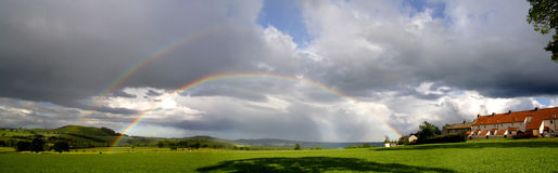 Rainbows and rain clouds Royalty Free Stock Images