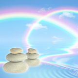 Rainbows and Spa Stones. Fantasy abstract of double rainbows against a blue sky with reflection over rippled water and floating grey spa stones in perfect Stock Photo