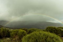 Rainbows on stormy day on the mountain stock images
