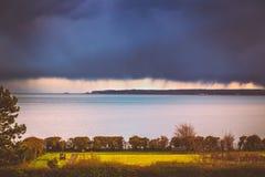 Rainclouds pesados sobre o horizonte e o negócio e sanduíche em Kent, Reino Unido enquanto a luz do sol em uma área do parque da  foto de stock