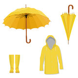 Raincoat, boots, umbrella. Yellow raincoat, rubber boots, opened and closed umbrella. Fashion protection Royalty Free Stock Photography