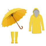 Raincoat, boots, umbrella. Yellow raincoat, rubber boots and opened umbrella. Fashion, protection Stock Images