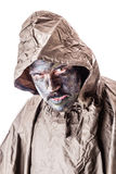 Raincoat soldier. A soldier wearing a poncho or raincoat and army camouflage face paint isolated over a white background Royalty Free Stock Images