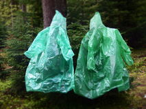 Raincoats like ghosts in the forest Stock Photo