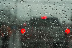 Raindrop on car window. Raindrop at window that show blur red light from car Royalty Free Stock Image