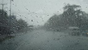 Raindrop on glass front of my car and wipers working while driving on road stock footage