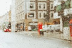 Raindrop on glass and red London bus lights background. Stock Image