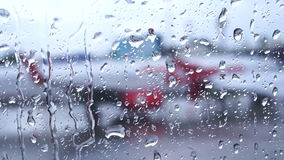 Raindrops on the air plane window with blur airport outside stock video
