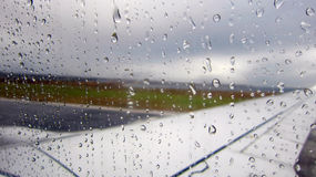 Raindrops on airplane window by the runway. A rainy day on an airport runway. Raindrops falling on the side glass window royalty free stock image