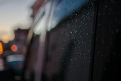 Raindrops on a black car on the side rear black window stock image