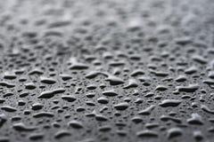 Raindrops on black metal surface Stock Photos