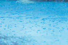 Raindrops in blue water Royalty Free Stock Photo