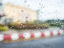 Raindrops on car glass with blurry footpath and building background. Royalty Free Stock Photo