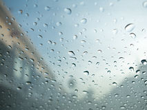 Raindrops on car's glass with blurry cloudy sky and village. Royalty Free Stock Images