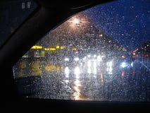 Raindrops on car window. Waiting at a crossing on a rainy november morning royalty free stock image