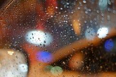 Raindrops on car window at night. Rainfall on car window with traffic jam in rainy season Royalty Free Stock Photos