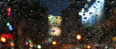 Raindrops on the car windshield during driving on the urban street at night Royalty Free Stock Images
