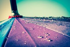Raindrops on a colorful umbrella with all the colors of the rainbow close-up macro waterdrops background. stock image