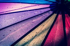 Raindrops on a colorful umbrella with all the colors of the rainbow close-up macro waterdrops background. stock photography