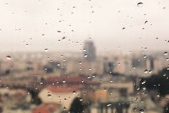 Raindrops on the dirty glass, behind the glass blurred panorama. Of the old colored city, abstract retro nostalgically background Stock Photo