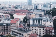 Raindrops on the dirty glass, behind the glass blurred panorama. Of old colored city, abstract retro nostalgically background stock image