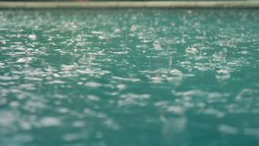 Raindrops fall into the water. Beautiful pool water surface under the rain. Slow motion. Beautiful pool water surface under the rain. Slow motion stock video footage