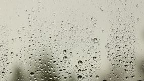 Raindrops fall on a window pane on a cloudy day. Bad weather outside. Sad and dull mood. Autumn depression. Solitude with thoughts. And yourself. Protection of stock footage