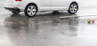 Raindrops are falling on a street with a moving car and toys Royalty Free Stock Photo