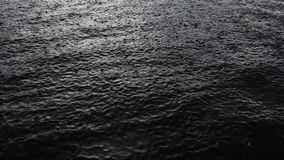 Raindrops falling on water surface stock footage