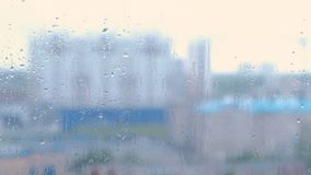 Raindrops flow down the window close-up. View of multi-building house from wet window, blur.  stock video footage