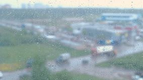 Raindrops flow down the window close-up. View of sity and road from wet window, blur. Raindrops flow down the window close-up. View of sity and road from wet stock footage