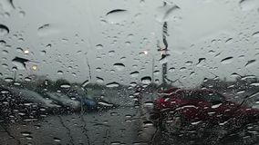 Raindrops flow down the windshield. View from inside the car. On the street runs a wet man. stock video footage