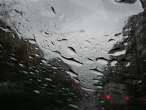 Raindrops forming streaks on a windshield Royalty Free Stock Photo