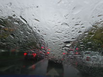 Raindrops forming streaks on a windshield Stock Image