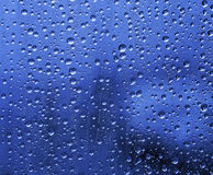 Raindrops on glass. In blue Stock Photography
