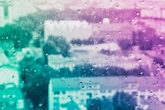 Raindrops on the glass, behind the glass blurred panorama of th royalty free stock image