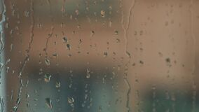 Raindrops on glass on a blurred background. Raindrops on glass on a blurry background on a rainy april spanish day stock footage