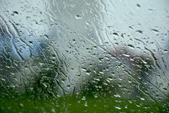 Raindrops on the glass. The croRaindrops on the car glassw sits on the index among the trees stock photo