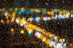Raindrops on the glass and the lights of the city at night. Raindrops on the glass and the lights Royalty Free Stock Photography