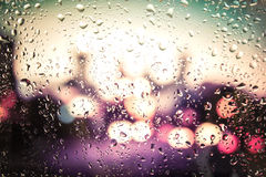 Raindrops on glass. Outside the window the evening street Stock Photo