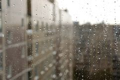 Raindrops on glass window against city background Royalty Free Stock Images