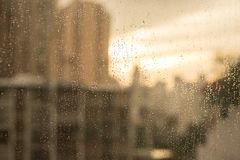Raindrops on glass window. with blur buildings and warm tone Royalty Free Stock Photography