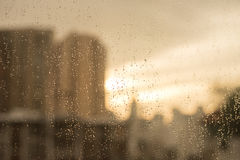 Raindrops on glass window. with blur buildings and warm tone Stock Images