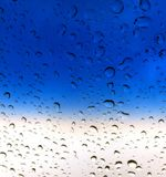 Rain Drops on a Glass Window Background. A close up of raindrops and blue sky seen through a glass window Royalty Free Stock Photos