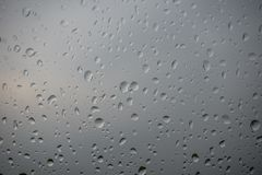 The raindrops on glass of a window stock photography