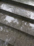 Raindrops on granite steps of outdoor staircase during rainy day Stock Images